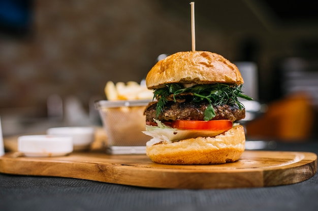 Side view of burger with beef cutlet herbs and tomato on a wooden board