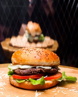 Side view of burger with beef meat melted cheese and vegetables on wooden board