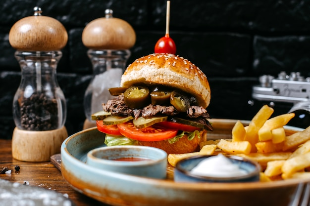Side view of burger with beef meat pickles and tomatoes served with french fries and sauces on black