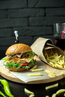 Side view burger with french fries and green pepper on blackboard