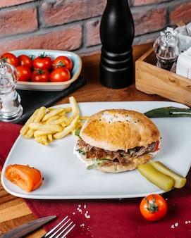 Vista laterale dell'hamburger con le patate fritte su una zolla bianca