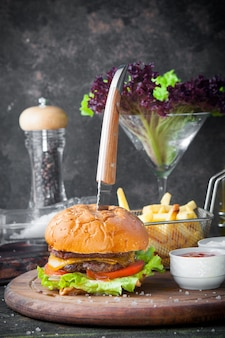 Side view burger with knife and bowl for sauce and french fries in wooden food tray on restaurant