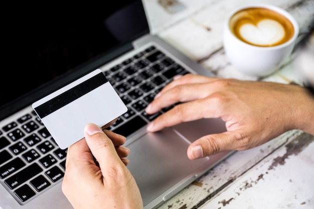 Вид сбоку деловой человек рука кредитной карты и использование ноутбука для интернета.