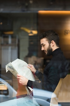 Side view business man reading newspaper