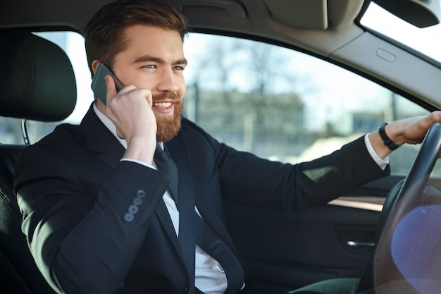 Side view of business man sitting at the wheel