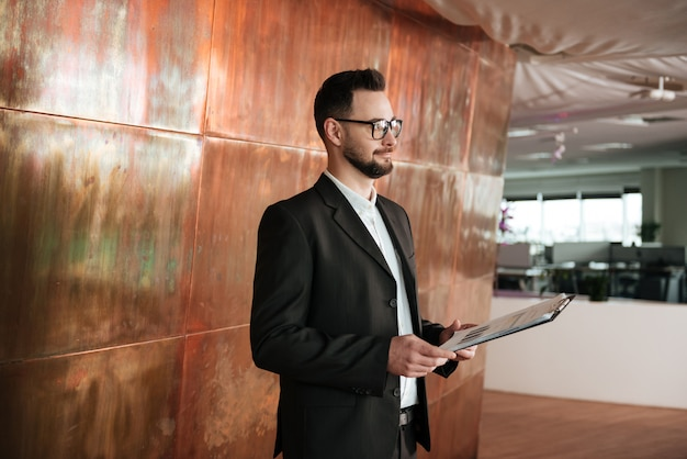 Side view of business man in suit with clipboard