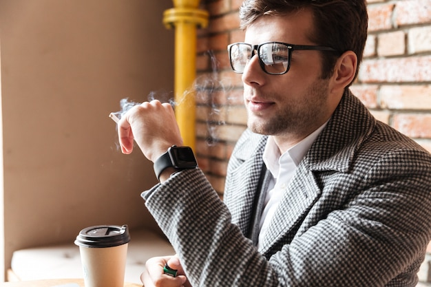 Side view of businessman in eyeglasses sitting by table