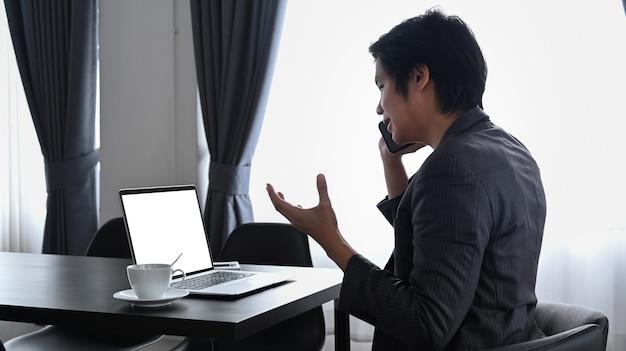 Вид сбоку бизнесмен сидит на современном рабочем месте и разговаривает по мобильному телефону.