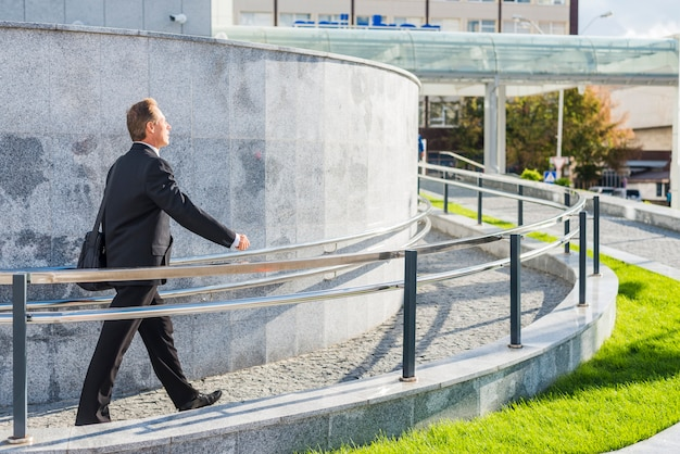 Side view of a businessman walking near railing