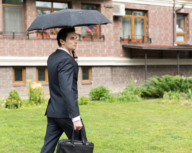 Side view of businessman with umbrella
