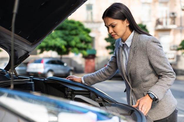 Vista laterale della donna di affari che controlla il motore dell'auto con il cofano alzato