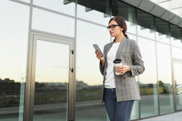 Side view of businesswoman checking smartphone outdoors while having coffee