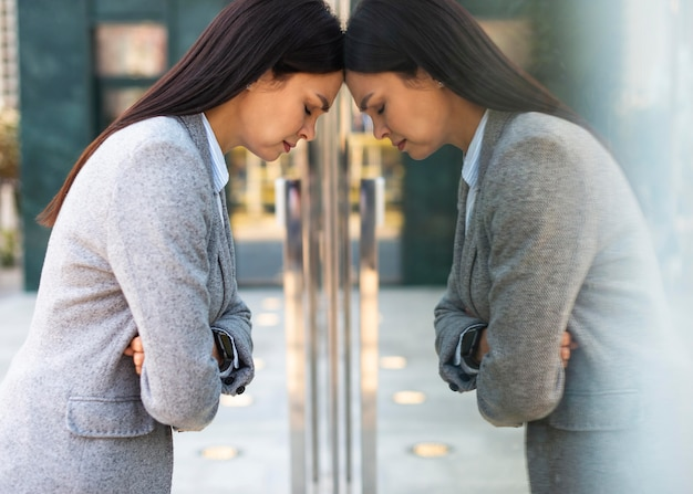 Side view of businesswoman leaning her head against glass door