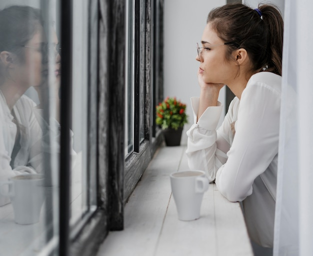 Donna di affari di vista laterale che osserva fuori