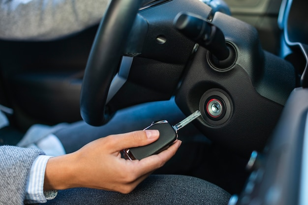 Side view of businesswoman using keys to turn on the car