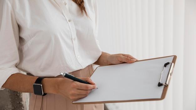 Vista laterale della donna di affari con i appunti