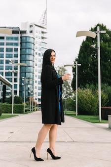 Vista laterale di una donna d'affari con tazza di smaltimento in piedi di fronte a edificio