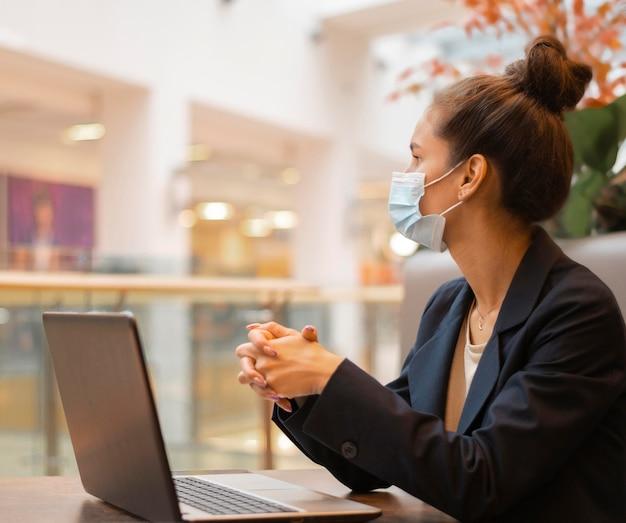 그녀의 노트북에서 일하는 의료 마스크와 측면보기 사업가