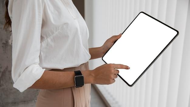 Vista laterale della donna di affari con la compressa