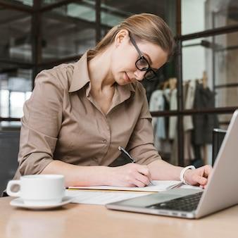 Vista laterale della donna di affari che lavora allo scrittorio con il computer portatile