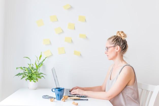 Vista laterale di una donna d'affari che lavora al computer portatile in ufficio