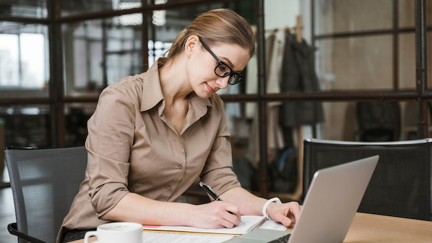 Side view of businesswoman working with laptop at desk
