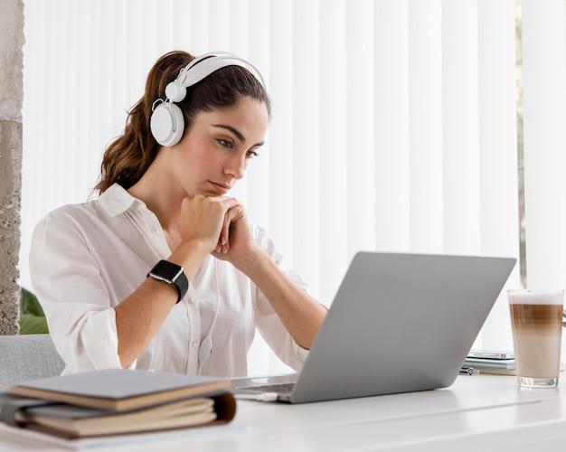 Vista laterale della donna di affari che lavora con il computer portatile e le cuffie
