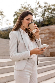 Side view of businesswoman working with smartphone and drinking coffee