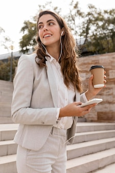 Side view of businesswoman working with smartphone and having coffee