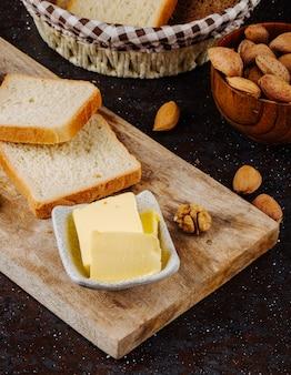 Вид сбоку сливочное масло с белым хлебом миндаля и грецкого ореха на доске