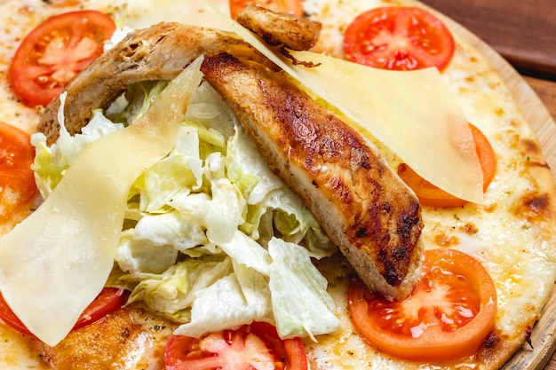 Вид сбоку пицца цезарь с жареной курицей помидор плавленый сыр, сыр пармезан и салат на доске