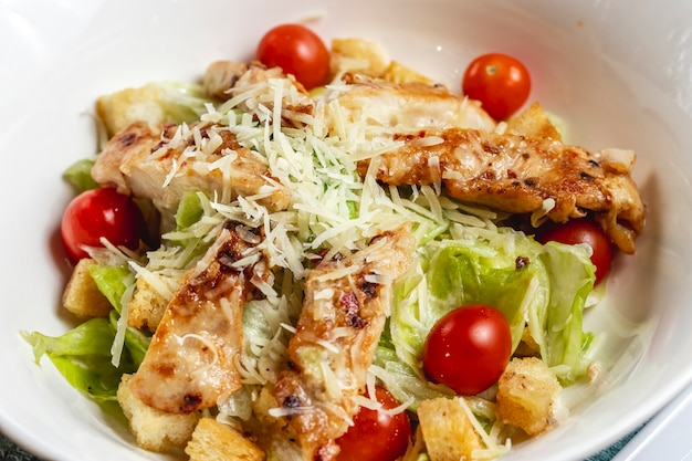 Side view caesar salad with cherry tomatoes parmesan grilled chicken and lettuce on a plate