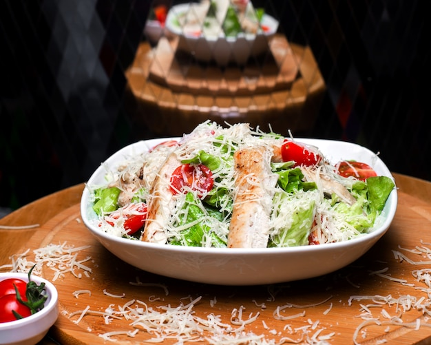 Side view of caesar salad with chicken and parmesan cheese in a white bowl on wooden board