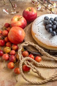 Vista laterale una torta una torta appetitosa con uva mele bacche corda rami degli alberi