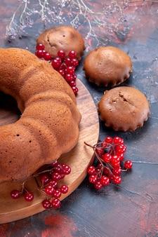 케이크와 붉은 건포도가 있는 커팅 보드 옆에 있는 사이드 뷰 케이크 컵케이크