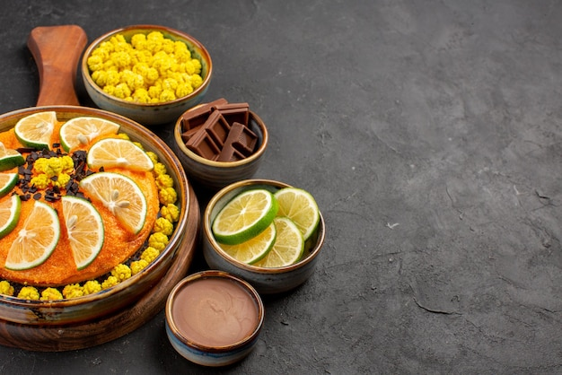 Torta vista laterale e ciotole al lime di caramelle al cioccolato crema al cioccolato e lime accanto all'appetitosa torta all'arancia sul tavolo
