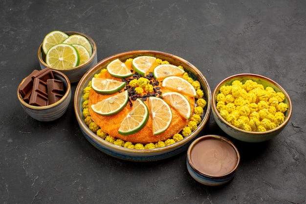 Side view cake and sweets appetizing cake with citrus fruits and bowls of chocolate cream yellow candies chocolate and slices of limes