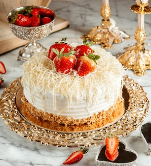 Side view of a cake with strawberries and crumbs on silver tray