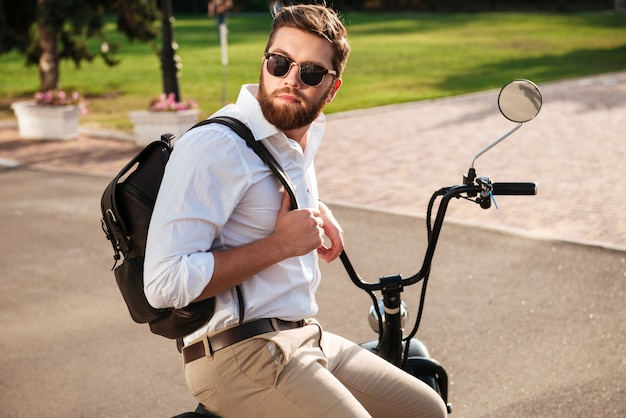 Side view of calm bearded man in sunglasses with backpack sitting on modern motorbike outdoors and looking away