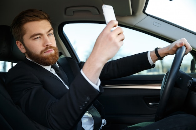 Side view of calm business man making selfie