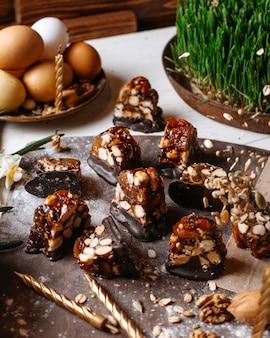 Vista laterale della caramella con caramello cioccolato fondente e nocciole tostate su una tavola di legno
