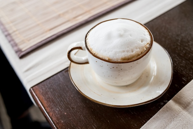 Side view cappuccino coffee in white cup on wooden table focus at white foam