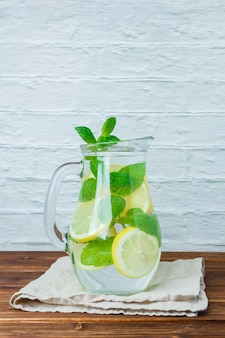 Side view carafe of lemon on white cloth on wooden and white surface. vertical space for text