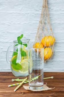 Caraffa di vista laterale di limone con cannucce, bicchiere vuoto su superficie in legno e bianca. spazio verticale per il testo