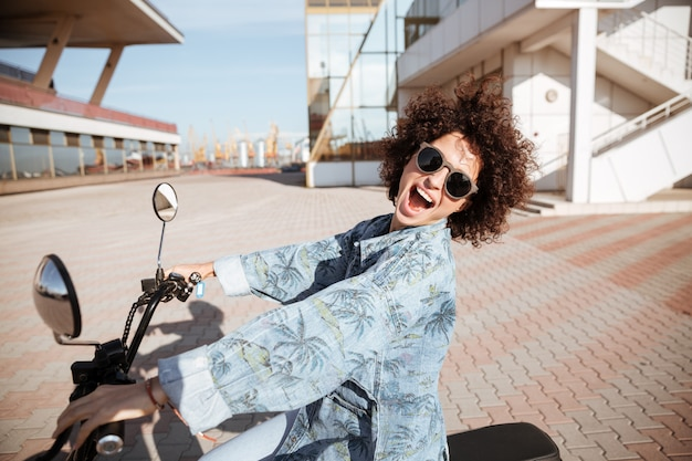 Side view of carefree happy curly woman in sunglasses posing on modern motorbike outdoors