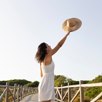 Side view of carefree woman outdoors with hat