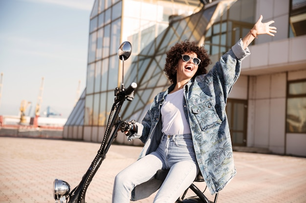 Side view of carefree woman in sunglasses sitting on motorbike
