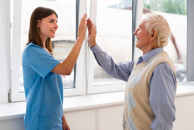Side view caregiver high fiving with old man