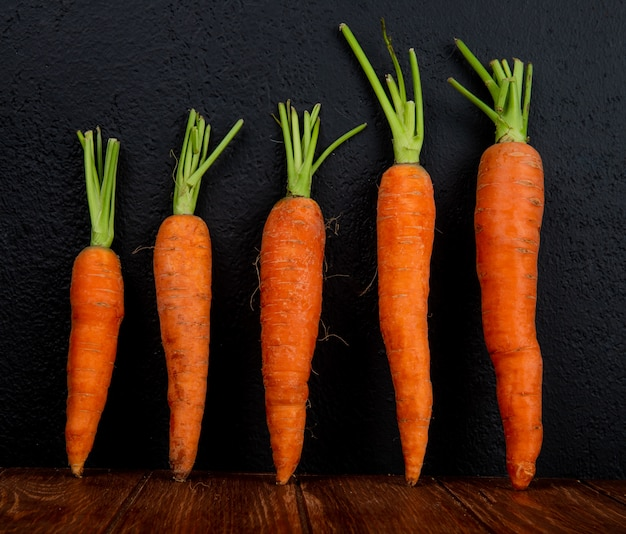 Side view of carrots on wooden surface and black background
