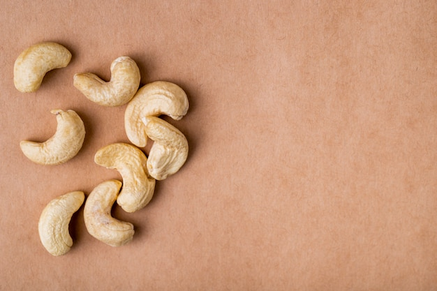 Side view of cashews on old paper texture background with copy space